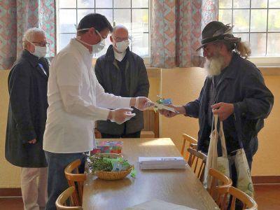 Bischof Dr. Franz Jung (hinten rechts) und Professor Dr. Klaus Reder von Sant'Egidio bei der Essensausgabe in der Elisabethstube.
