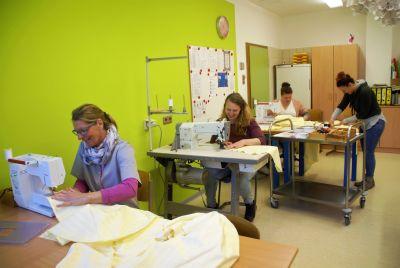 Mitarbeiterinnen der Caritas-Don Bosco gGmbH nähen Schutzkittel für Pflegekräfte.