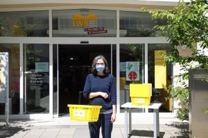 LWB-Leiterin Anne Große-Schulte zeigt, was man beim Betreten der Bücherei beachten sollte: Erforderlich sind ein Mund-Nasen-Schutz und ein Korb.