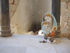 Teilweise zerstörte Mutter Maria mit dem Jesuskind. Büste am 29. September 2017 auf dem Altar der griechisch-orthodoxen Kirche in der Altstadt von Zabadani (Syrien). Davor eine abgebrannte Kerze und Weihrauch.