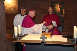 Nach dem Ablegen des Kapitelseids setzte Dompropst Weihbischof Ulrich Boom (2. von links) Domdekan Dr. Jürgen Vorndran (kniend) das Birett auf den Kopf.