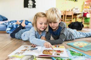 Zwei Geschwister, ein Mädchen und ein Junge, liegen am 26. September 2016 auf dem Boden im Wohnzimmer in Bonn und lesen gemeinsam in einem Kinderbuch. Die Schwester zeigt ihrem Bruder mit dem Finger ein Bild in dem Bilderbuch.