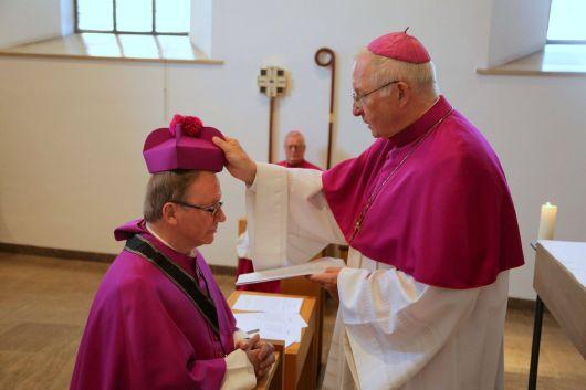 Im Mai 2015 wurde Generalvikar Thomas Keßler (links) Domkapitular. Dompropst Weihbischof Ulrich Boom setzt ihm das Birett auf den Kopf.