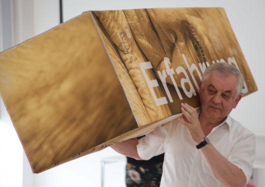 Pfarrer Stefan Mai hat sch eine Stele geschnappt und positioniert diese neu im Raum.