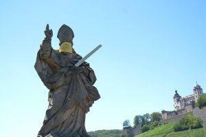 """""""Wir halten seit 295 Jahren Abstand!"""": Auch der heilige Kilian auf der Alten Mainbrücke trägt vorübergehend einen Mund-Nasen-Schutz."""