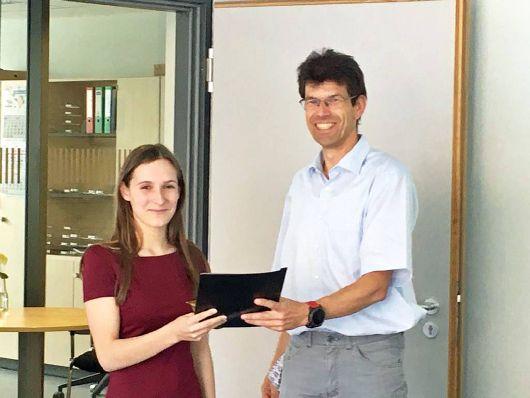 Michael Seufert, Leiter der Abteilung Informationstechnologie (IT) der Diözese Würzburg, überreicht Luisa Fiore das Abschlusszeugnis als Fachinformatikerin.