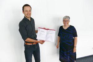 Marcus Marquart (links) mit dem Zeugnis über den erfolgreichen Abschluss seines Masterstudiums. Rechts Rektorin Dr. Ursula Silber.