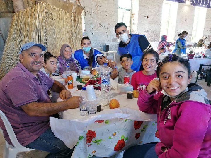 Helfer von Sant'Egidio beim Abendessen im Gespräch mit Menschen aus dem Lager Moria.