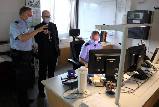 Polizeidirektor Dr. Sven Schultheiß (links) erläutert Bischof Dr. Franz Jung (2. von rechts) die Einsatzleitstelle.