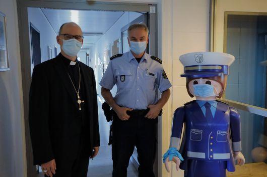 """Gruppenbild mit Dame (von links): Bischof Dr. Franz Jung, Polizeidirektor Dr. Sven Schultheiß und Polizeihauptkommissarin """"Pia"""", das Maskottchen der Bundespolizeiinspektion Würzburg."""