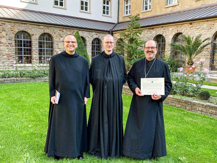 Novizenmeister Pater Frank Möhler, Bruder Denis Schmelter und Abt Michael Reepen mit der Professurkunde (von links).