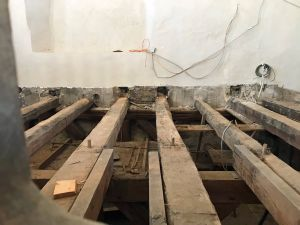Blick in den geöffneten Boden der Orgelempore und auf die nun freiliegenden jahrhundertealten Stützbalken.