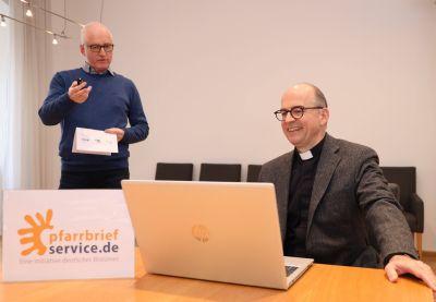 Pastoralreferent Johannes Simon (links), Leiter von pfarrbriefservice.de, erläutert im Würzburger Bischofshaus Bischof Dr. Franz Jung die wichtigsten optischen Veränderungen des Internetportals, das in diesen Tagen seinen 18. Geburtstag feiert.