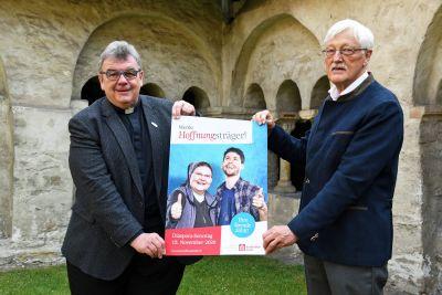 Monsignore Georg Austen (links), Generalsekretär des Bonifatiuswerks, und Präsident Heinz Paus präsentieren das Leitmotiv zur bundesweiten Diaspora-Aktion 2020.