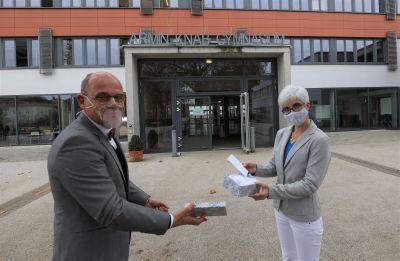 Schulreferent Jürgen Engel übergibt eine der gespendeten transparenten Coronamasken an Oberstudienrätin Anette Gerhard, die sich in der Schulpastoral am Kitzinger Armin-Knab-Gymnasium engagiert.