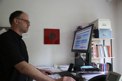 Pfarrer Thomas Menzel zeigt den Dienstplan seines Teams.