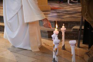Pfarrer Thomas Menzel entzündet die Kerzen der Kommunionkinder.