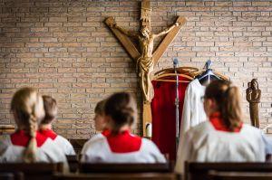 Ministrantinnen vor einem Kruzifix aus Holz.