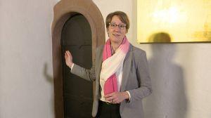 Alexandra Eck, Referentin für die Dombesucherpastoral, im ersten Adventsimpuls vor einer Tür im nördlichen Seitenschiff des Kiliansdoms. Die Tür führt hinauf zur Orgel und zum Glockenturm.