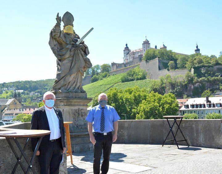 Weihbischof Ulrich Boom (links) unterstützt am 31. Juli einen Appell der Stadt Würzburg an die Menschen, sich in Corona-Zeiten verantwortungsvoll zu verhalten. Im Rahmen der Aktion tragen die Brückenheiligen auf der Alten Mainbrücke einen Vormittag lang Mund-Nasen-Schutz.