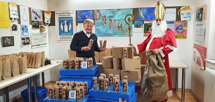 Der Nikolaus der Katholischen jungen Gemeinde (KjG) im Diözesanverband Würzburg übergibt am 2. Dezember 250 Schokoladen-Nikoläuse an Stefan Labus (links), Leiter der Schweinfurter Kindertafel.