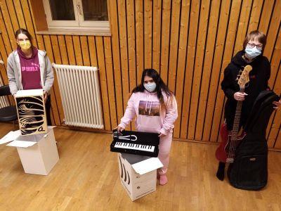 """Die Teilnehmerinnen Jasmin Greller, Saba Hussein und Svenja Zösch freuen sich über die Spende des """"New Future""""-Chors und die neuen Musikinstrumente."""