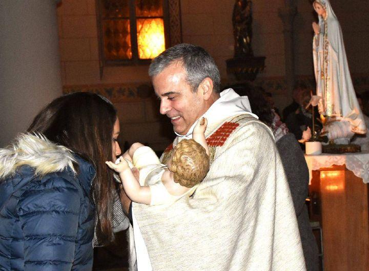 Padre Dr. Joaquim Carneiro da Costa hält nach der portugiesischen Tradition die Figur des Jesus Kindes während die Gemeindemitglieder nach vorne kommen und es küssen. Das Bild entstand Weihnachten 2019, vor der Corona Pandemie.
