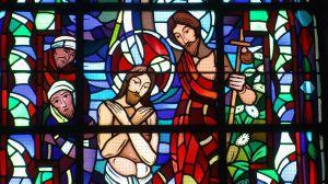 Ein Glasfenster zeigt Johannes den Täufer, der Jesus im Jordan tauft. Das Bild zeigt außerdem zwei Zuschauer.