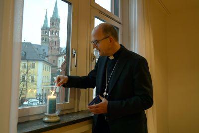 Bischof Dr. Franz Jung entzündet in einem Fenster des Bischofshauses eine Kerze zum Gedenken an die Verstorbenen und deren Angehörige in der Coronakrise.