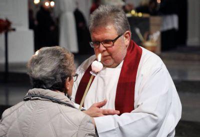 Ein Priester beim Erteilen des Blasiussegens. In diesem Jahr unterliegt der Segen den geltenden Corona-Schutzmaßnahmen.