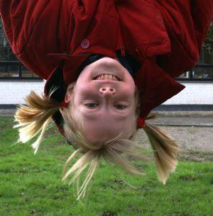 Ein lachendes Mädchen schaut kopfüber in die Kamera. Möglicherweise lässt sich das Kind von einer Turnstange herabhängen.