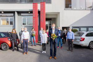Betriebsleiter und Mitarbeiter der Geschäftsstelle begrüßen Christoph Vogel (vorne mit Blumenstrauß) als neuen Geschäftsführer der Vinzenz Werke.