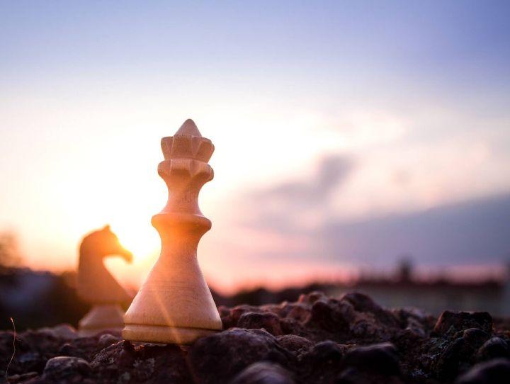 Zwei Schachfiguren, ein König und ein Pferd, stehen auf der Erde, während im Hintergrund die Sonne untergeht.