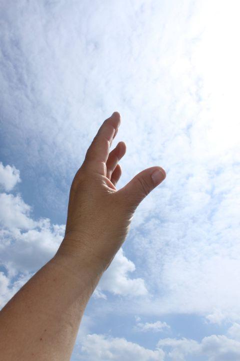 Eine ausgestreckte Hand greift nach dem Himmel. Sie symbolisiert die Sehnsucht nach Berührung mit dem Göttlichen.
