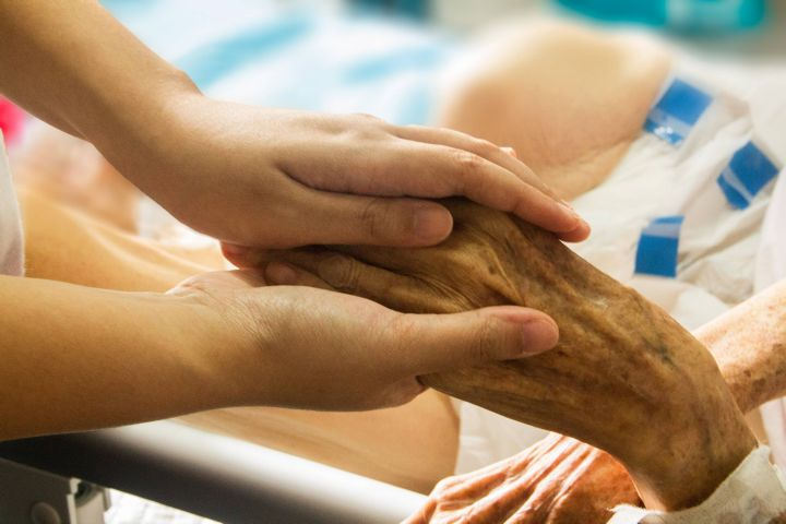 Zwei Hände halten die linke Hand eines alten Menschen. Die Szene ist an einem Krankenbett aufgenommen.