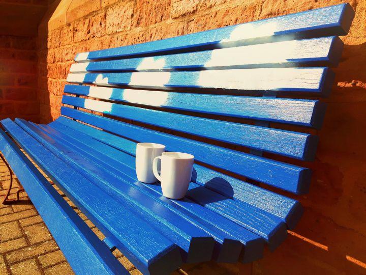 Auf einer blauen Sitzbank stehen zwei Tassen, welche die Begegnung von Personen symbolisieren.