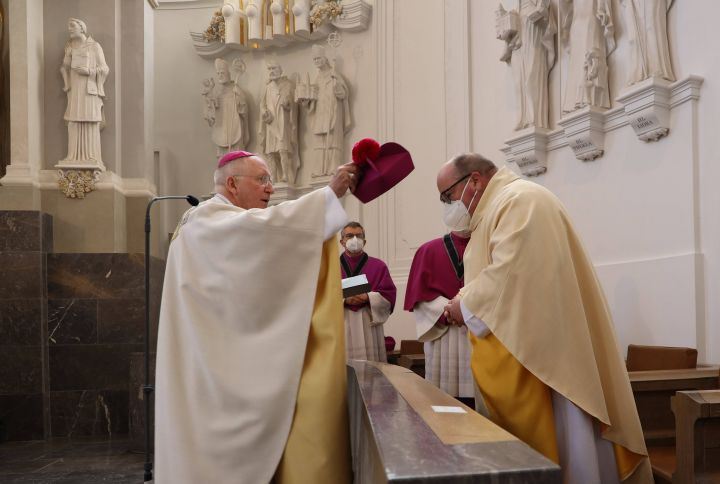 Dompropst Weihbischof Ulrich Boom (links) führte Domkapitular Stefan Gessner an seinen Platz im Chorgestühl des Kiliansdoms und setzte ihm das Birett auf.