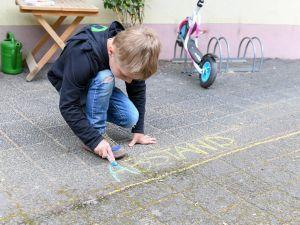 """Ein Junge malt mit Kreide das Wort """"Abstand"""" an einer Markierung vor seinem Kindergarten nach."""