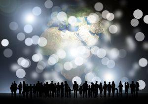 Frauen, Männer und Kinder stehen vor einer großen Weltkugel. Die Kontinente sind golden gefärbt. Das Bild symbolisiert die Verbundenheit von Menschen weltweit.