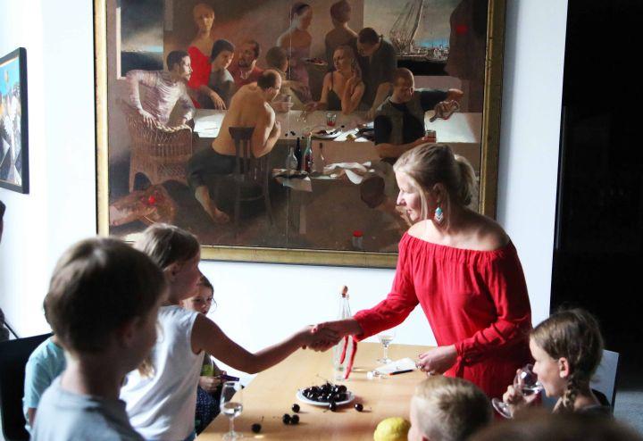 """Veranstaltung """"Nachts im Museum"""" im Museum am Dom:  Museumsführerin Sandra Miara-Hegent (im roten Kleid) begrüßt die Kinder. Sie verkörpert eine Figur aus dem Gemälde """"Die Würfel"""" von Paulis Postažs."""