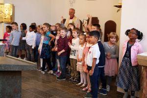 Domdekan Prälat Günter Putz, Schulreferent des Bistums Würzburg, segnet die Erstklässler der privaten katholischen Volksschule Elisabethenheim. Die Kinder winken ihren Eltern fröhlich zu.